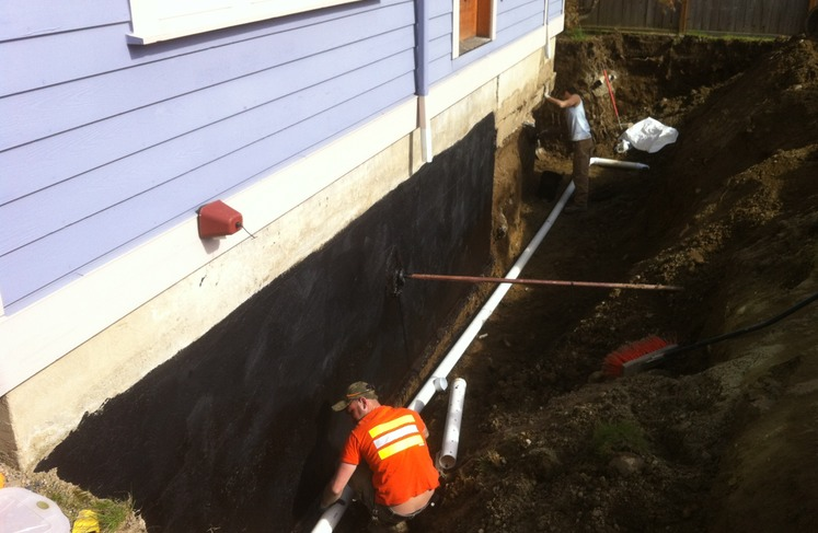footing drain and drain mat across a basement wall in seattle